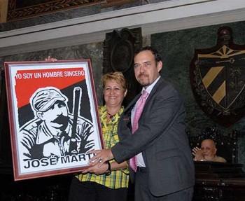 Aixa Hevia entrega un cuadro a Raúl Garcés, en reconocimiento especial a la Facultad de comunicación de la UH.